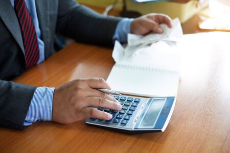 businessman hand using calculator for calculate tax in office.concept