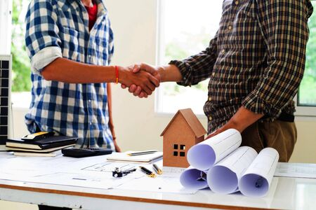 Team Engineers are shaking hand  solar panel Business for home construction designs to bring them to prospective customers.concept