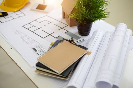 Desk of Architectural working solar panel home project in construction site,With drawing equipment concept.
