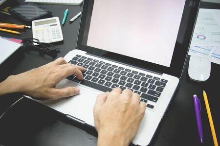 biznesmen pracujący używa laptopa w biurze do omawiania dokumentów i pomysłów, z nieostrością, z odcieniem vintage