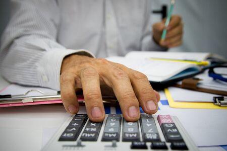 Geschäftsmann, der Taschenrechner verwendet und Geld hält, um Steuern im Amt zu berechnen. Standard-Bild