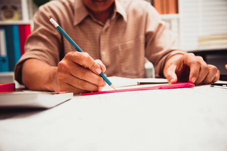 Businessman hand writing with document at work office