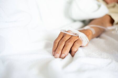 hand of the patient who is receiving the saline solution in the room of the patient in the hospital who is suffering from diarrhea. Stock fotó