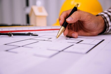 Close-up hand of male Architect drawing blueprint on work space in construction site. Banque d'images