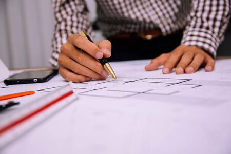 Close-up hand of male Architect drawing blueprint on work space in construction site.