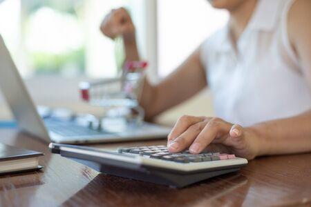 Geschäftsfrauen, die Taschenrechner verwenden und Karte zum Online-Shopping im Home Office halten
