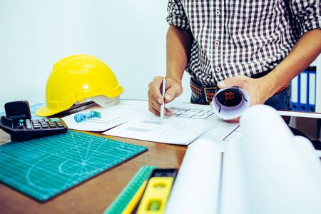 Engineer man and Architect drawings blueprint at Construction Site.Home Project to Offer Management