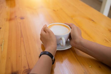 Hand Women put a Latte arts coffe hot coffee on wooden table.barista love art concept.