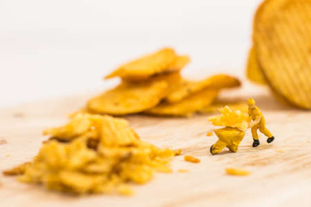 Miniature people, Workers work on production potato chips on white background (food concept)