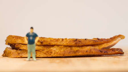 Miniature people, Close up fat man with grilled pork neck on white background with copy space