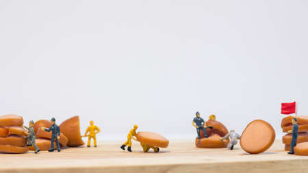 Miniature people : Close up workers work on sausages isolated on white background (food concept)