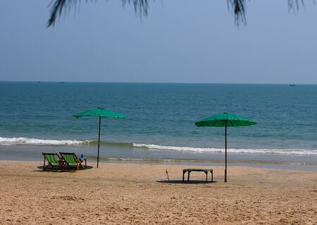 Beach chairs and colorful umbrella on the beach in sunny day,