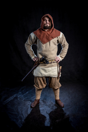 Young bearded man in a viking age clothing and hood with an ax