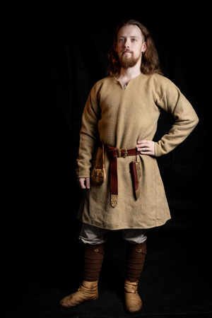 edhead long-haired young man in casual clothes of the Viking era
