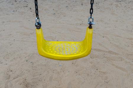 chain swing ride: yellow chain swings on playground