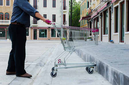 man pushing: man pushing a shopping cart in car park Stock Photo