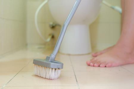 empleadas domesticas: Mujer cleanning un cuarto de ba�o con el cepillo Foto de archivo
