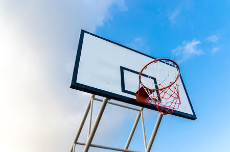 ou: Basketball hoop on blue sky and clouds