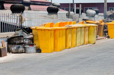bins: yellow plastic rubbish bins outside a building