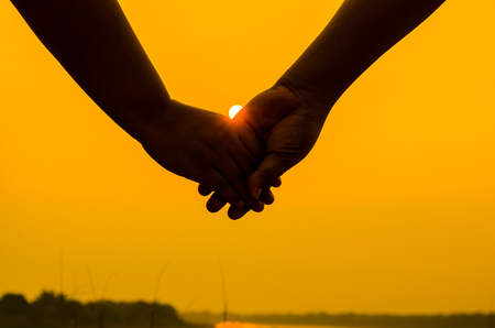 clasped hands: Romantic couple with clasped hands backlit by a bright evening sun in a closeup conceptual image of love