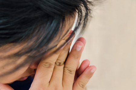 crossed fingers: sad young woman crossed fingers for her face in crisis moment
