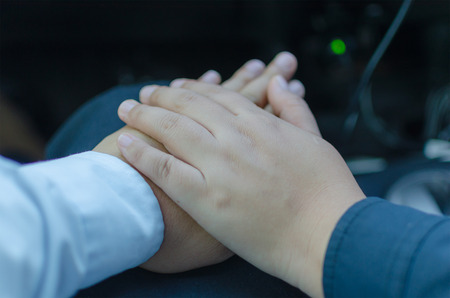 clasped hands: Romantic couple with soft clasped hands closeup conceptual image of love Stock Photo