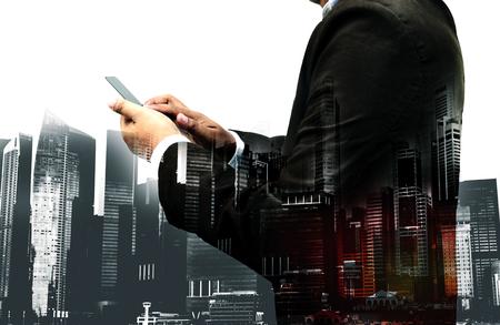 Double exposition de succès d'affaires en utilisant smartphone avec paysage urbain fond