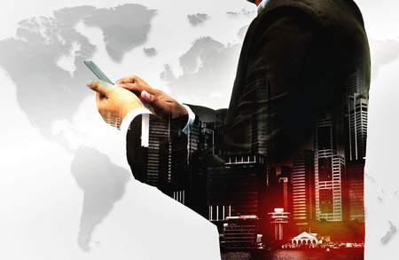Double exposure - businessman using smartphone with city overlay and world map background isolated on white background
