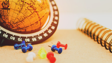 Pin and World globe map on wooden desk. Concept point or pin to goal and  destination with planning.