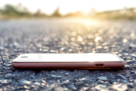 Smartphone on stone with bokeh and sunset background. Imagens