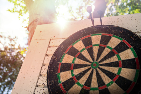 Old target dartboard with wooden background under sunset. Stock Photo