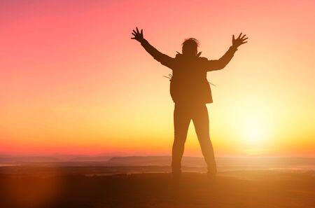 Schattenbild des glücklichen Mädchens, das auf Sonnenunterganghintergrund springt. Freiheit und genießen Konzept. Standard-Bild
