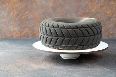 Modern designer chocolate cake in the shape of a car tire as a gift to a motorist or racer - the cake consist of mousse and covered dark chocolate on a stand - copy space and side view