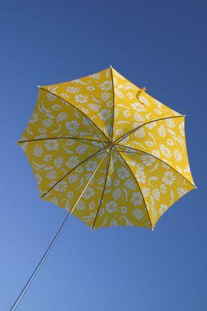 Yellow umbrella in blue sky