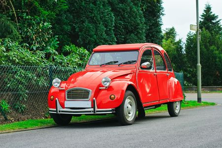 French red Citroen 2 cv parked in a street photo