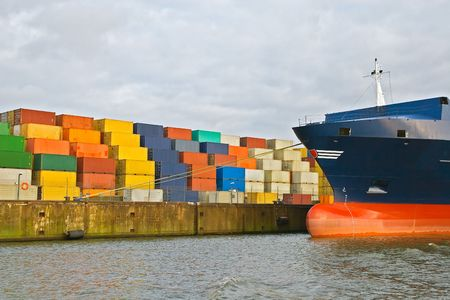 Hamburg, Germany - January 29, 2009: cargo freight containers stacked at harbor terminal with big containership