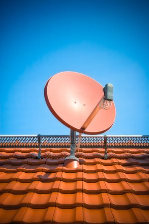 satellite tv: Satellite dish on roof with clear blue sky