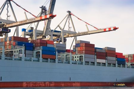 Unloading huge cargo freight container ship at harbour terminal Stock Photo