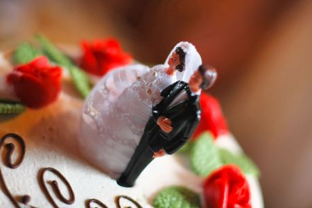 bride and groom figurine on top of a wedding cake - selective focus Stock Photo
