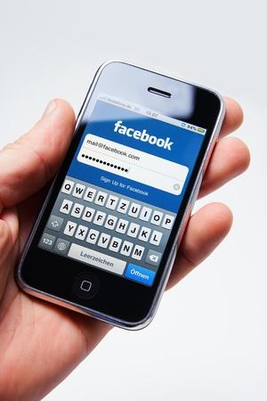 Münster, Allemagne - le 14 mars 2011 : Main tenant un iphone avec la version mobile du site www.facebook.com. Facebook est le site de réseautage social plus grand du monde, détenu par Joining Facebook, Inc., le réseau est gratuit.
