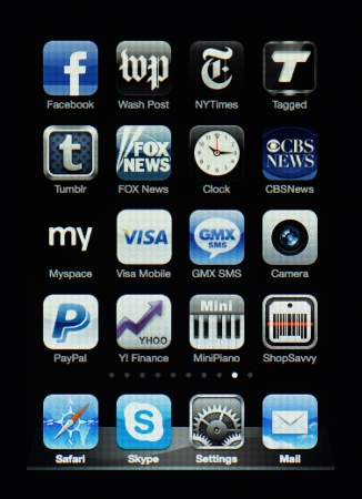 Muenster, Germany, April 16, 2011: Image of the iphone touch screen. Display shows a collection of useful apps with blue and grey color scheme. Stock Photo - 9338412