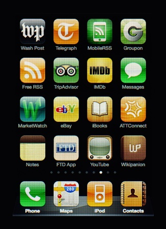 Muenster, Germany, April 16, 2011: Image of the iphone touch screen. Display shows a collection of useful apps with orange and green color scheme.