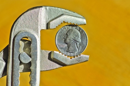 penny pinching: Close up of an Dollar Coin between pliers, concept of financial crisis