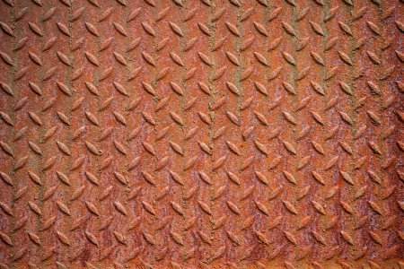 Photography shows a rusty metall background with diamond pattern.