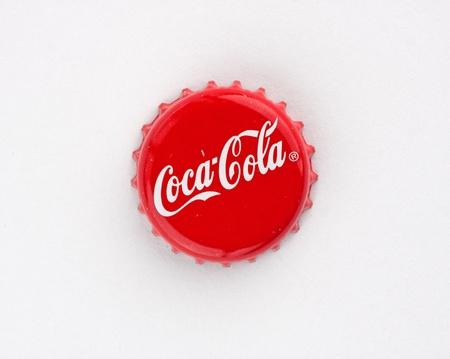 colas: Muenster, Germania - 10 Settembre 2011: la foto illustra tappo della bottiglia di coca cola su sfondo rosso. Editoriali