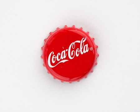 Muenster, Germany - September 10, 2011: Picture shows coca cola bottle cap on red background.