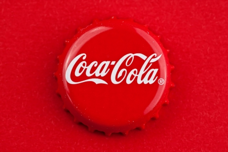 cola: Muenster, Germany - September 10, 2011: Picture shows coca cola bottle cap on red background.