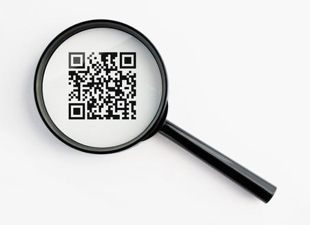 qr-code under a magnifying glass, with isolated background Stock Photo