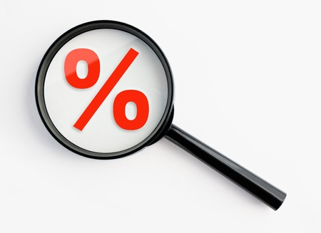 percentage sign under a magnifying glass, with isolated background photo