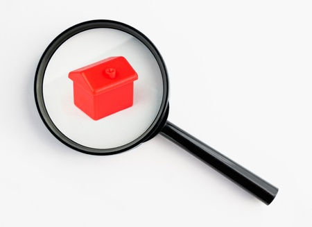 Muenster, Germany - November 6, 2011: Red plastic house under a magnifying glass from the famous property trading board game Monopoly, isolated on white. Monopoly is owned and manufactured by Hasbro.